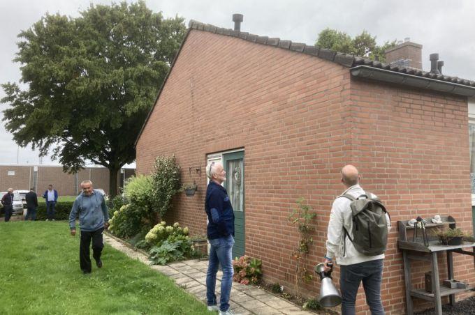 Energie-adviseur inspecteert met bewoners woning aan de buitenkant