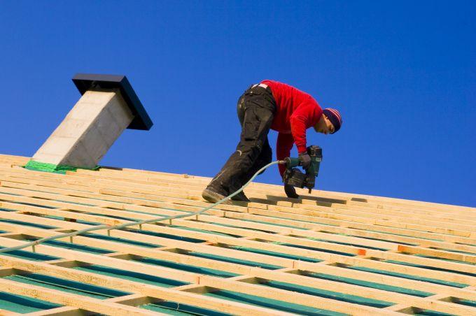 Bouwvakker op dak om isolatie aan te brengen