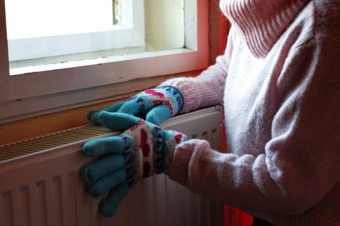 Handen verwarmen op de radiator met wanten aan