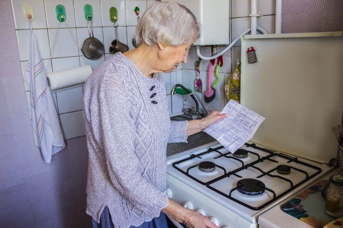 Oudere dame bekijkt energierekening bij gasfornuis