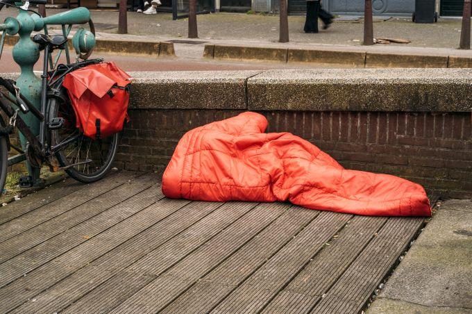 Persoon in slaapzak slaapt buiten