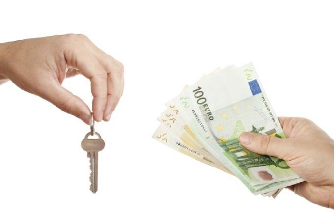 Hand met huissleutel en hand met geld