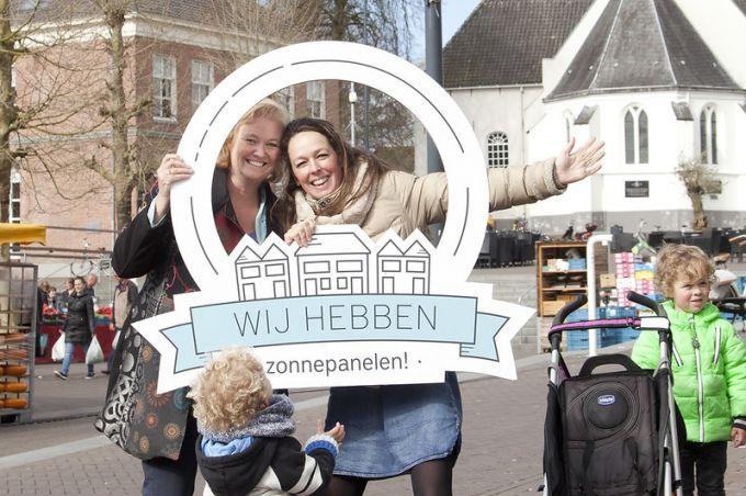 Twee vrouwen met een bord 'Wij hebben zonnepanelen'