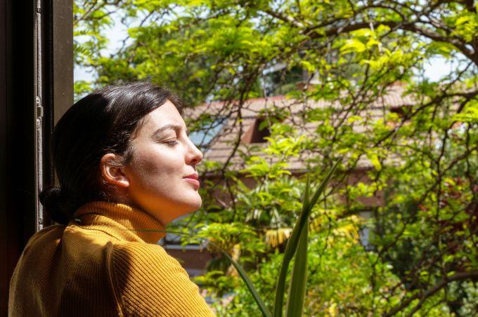 Vrouw geniet van de zon door het open raam