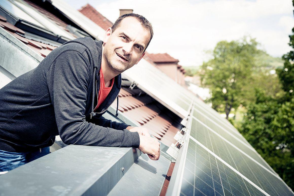 Bewoner kijkt uit dakraam naar zonnepanelen op de woning