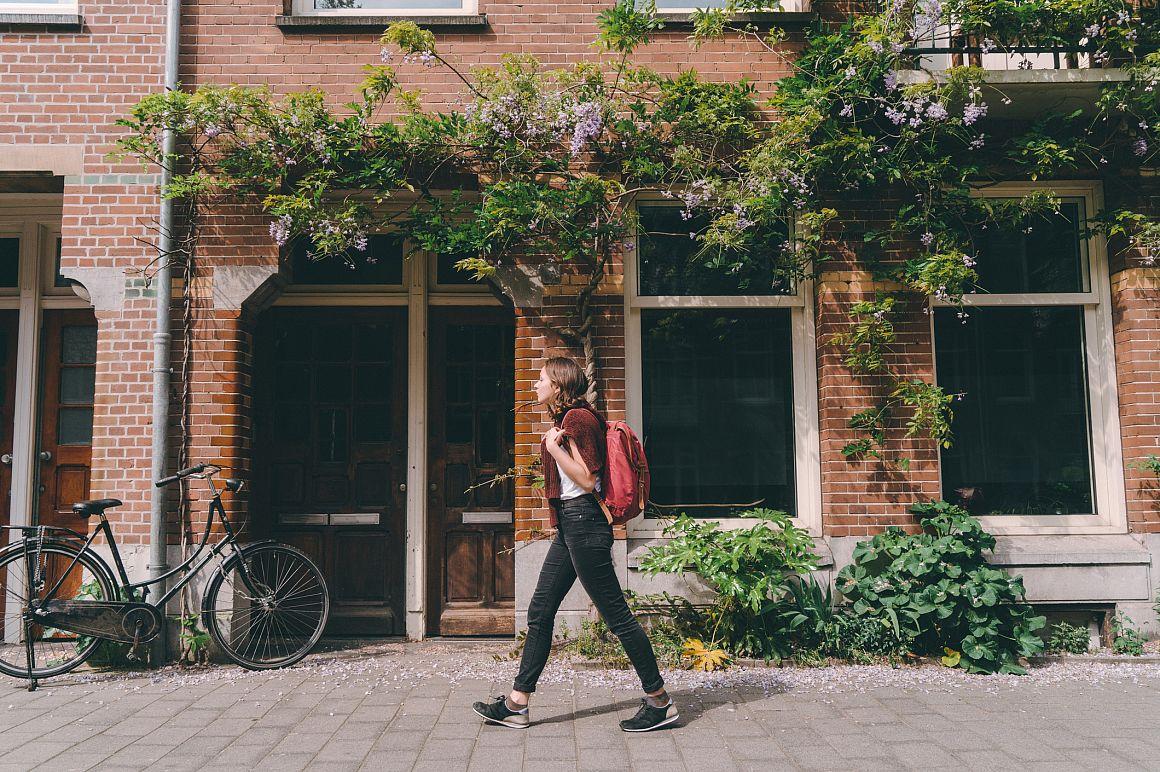 Vrouw loopt langs gevel met geveltuintje