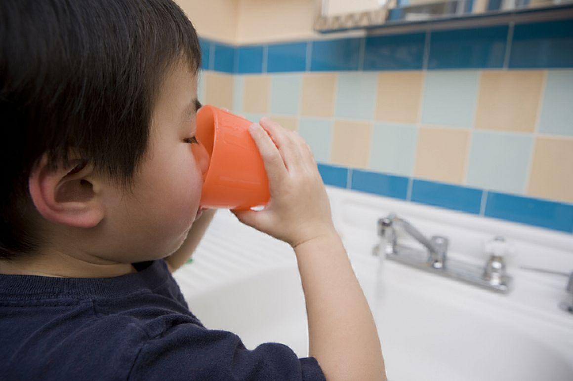 Klein kind drinkt een beker water bij de kraan