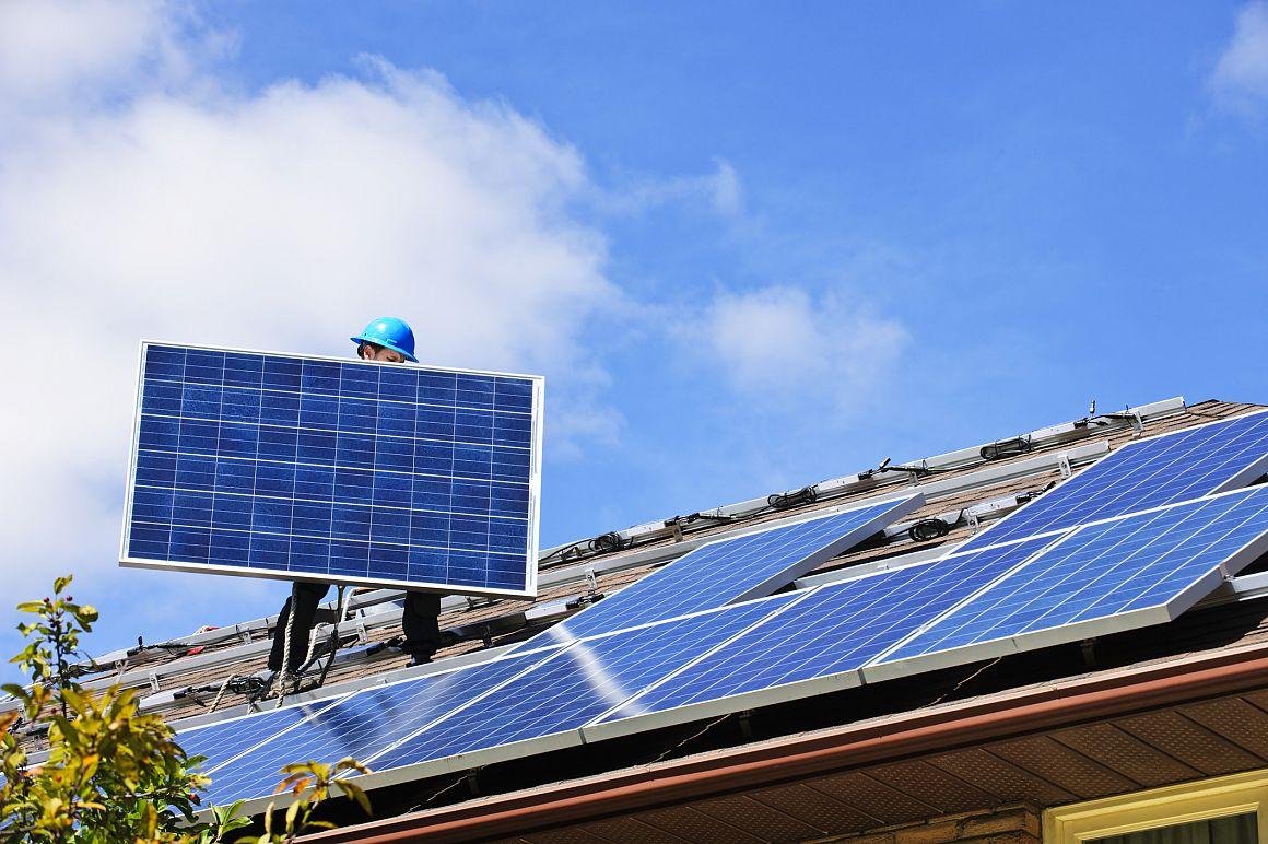 Man installeert zonnepanelen op dak van woning