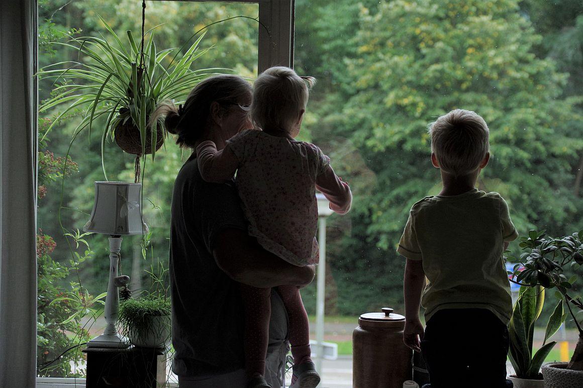 Moeder met kleine kinderen voor het raam