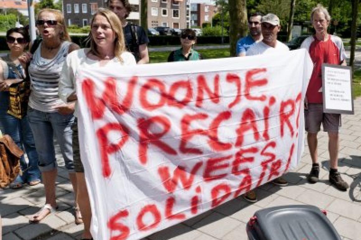 Demonstranten met spandoek Huur je precair, wees solidair