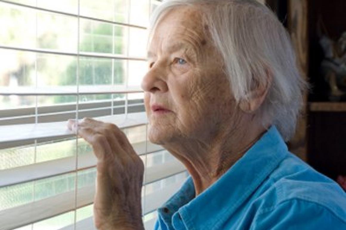 Oude dame kijkt uit het raam
