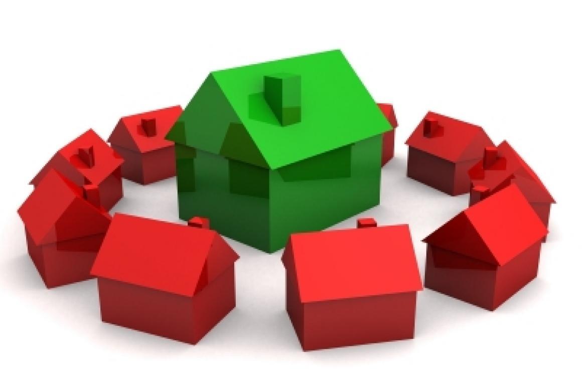 een groen huisje temidden van rode huisjes