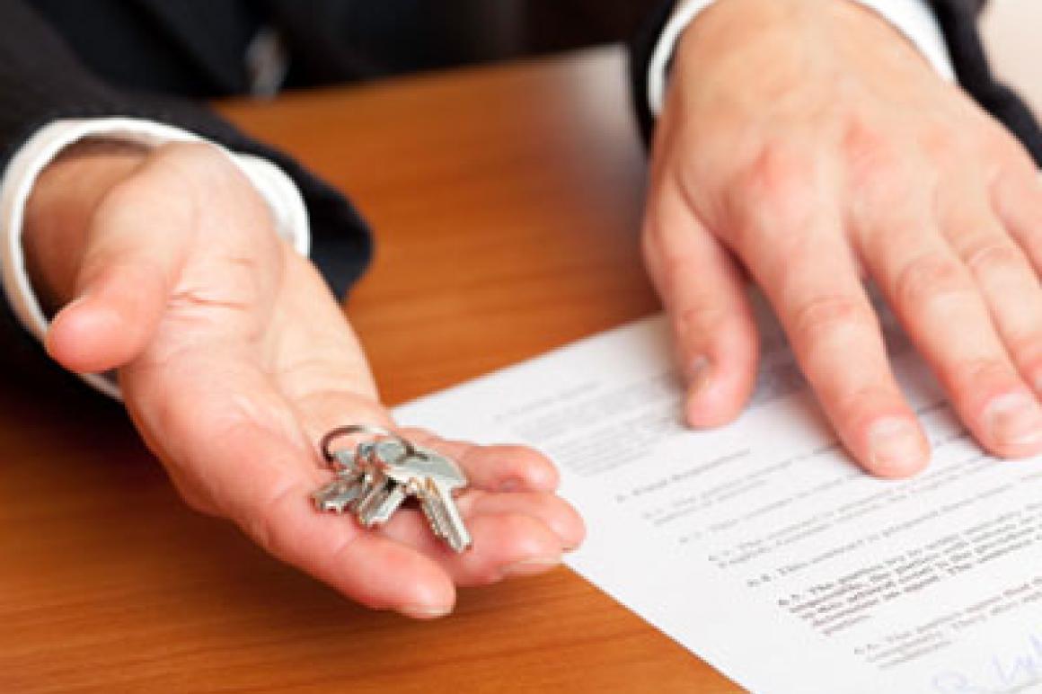 in ene hand sleutels, in andere hand huurcontract