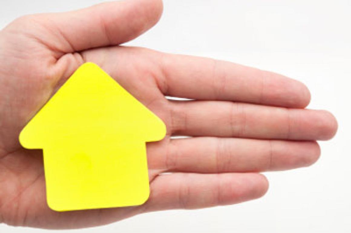 Hand met post-it in vorm van huisje