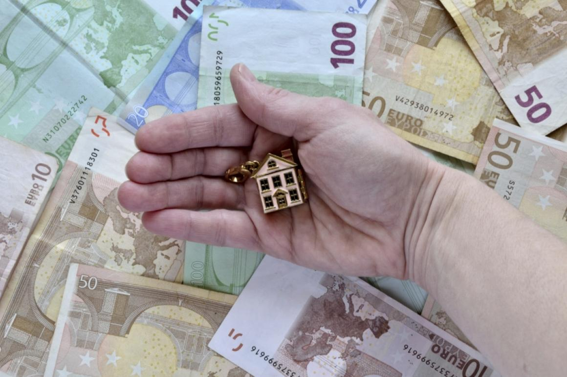 Hand met sleutelhanger van huisje voor stapel eurobiljetten