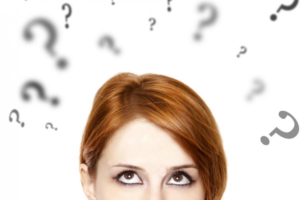 Jonge vrouw met vraagtekens boven haar hoofd