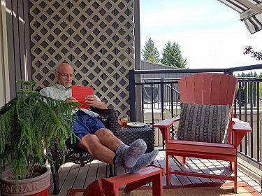 Oudere man zit onder zonnescherm voor zijn woning