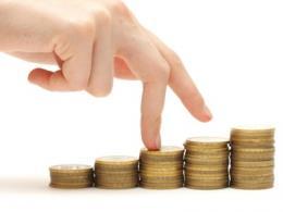 hand met steeds hogere stapeltjes euromunten