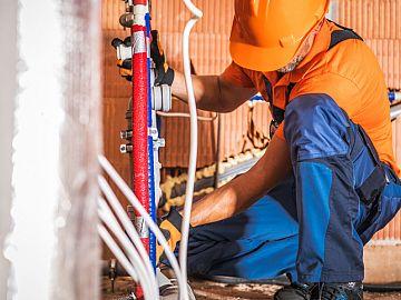 Loodgieter legt waterleidingen aan in huis