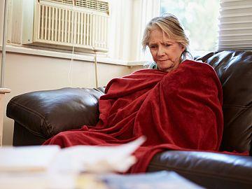 Vrouw thuis op de bank met deken om zich heen