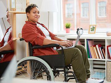 Jonge vrouw in rolstoel op thuiswerkplek