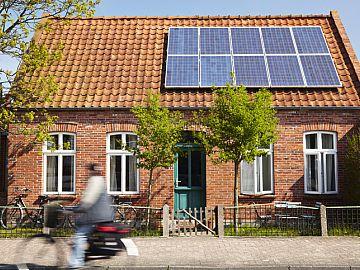 Klein oud huisje met zonnepanelen op het dak