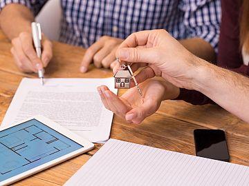 Hand houdt sleutel van woning vast