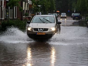 Auto rijdt door overstroomde straat met huizen