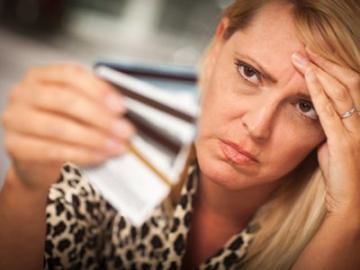 vrouw kijkt met zorgelijk gezicht naar betaalpasjes