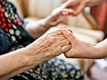Bejaarde dame wordt uit stoel geholpen