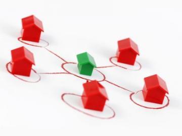 groen huisje temidden van 5 rode huisjes