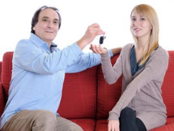 Oudere man overhandigt sleutel aan jonge vrouw