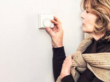 vrouw draait thermostaat hoger
