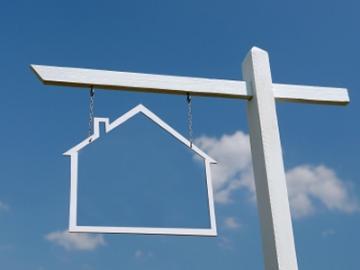 huisje aan uithangbord met wolkenlucht