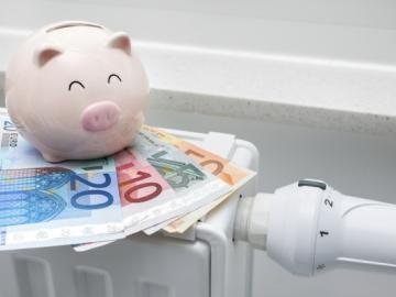 Spaarvarken met geld op radiator