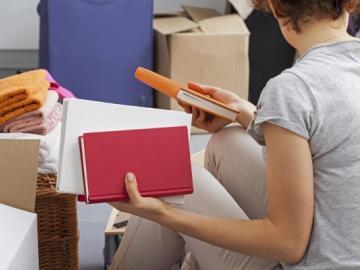 Jonge vrouw pakt spullen in voor verhuizing
